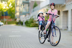 Young mother and her toddler girl riding a bicycle Stock Photos