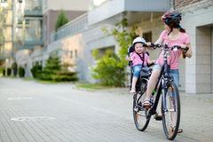 Young mother and her toddler girl riding a bicycle Royalty Free Stock Photos