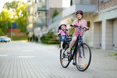 Young mother and her toddler girl riding a bicycle Royalty Free Stock Photo