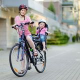 Young mother and her toddler girl riding a bicycle Stock Images