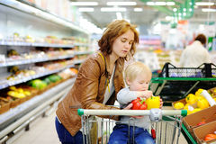 Young mother and her toddler son in a supermarket Stock Photography