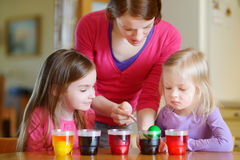 Young mother and her two daughters painting Easter eggs Royalty Free Stock Photo