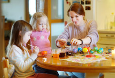 Young mother and her two daughters painting Easter eggs Royalty Free Stock Images