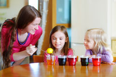 Young mother and her two daughters painting Easter eggs Stock Photos