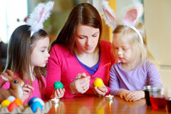 Young mother and her two daughters painting Easter eggs Royalty Free Stock Photography