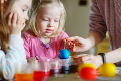 Young mother and her two daughters painting Easter eggs Royalty Free Stock Photos