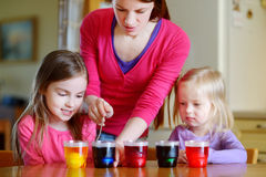 Young mother and her two daughters painting Easter eggs Stock Photography