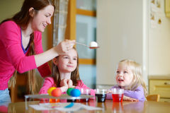 Young mother and her two daughters painting Easter eggs Stock Images