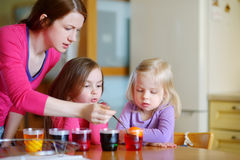 Young mother and her two daughters painting Easter eggs Stock Photo