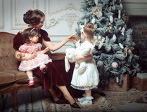 Young mother and her two little daughters near Christmas tree Stock Photography