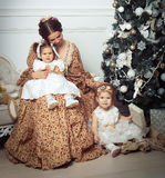 Young mother and her two little daughters near Christmas tree Royalty Free Stock Photography