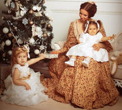 Young mother and her two little daughters near Christmas tree in Stock Photos