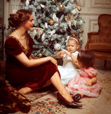 Young mother and her two little daughters near Christmas tree in Royalty Free Stock Photography