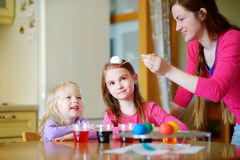 Young mother and her two little daughters painting colorful Easter eggs Royalty Free Stock Images