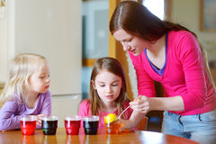 Young mother and her two little daughters painting colorful Easter eggs Stock Photography