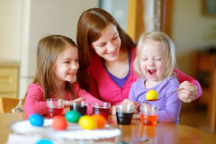 Young mother and her two little daughters painting colorful Easter eggs Stock Photo