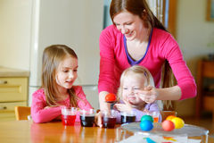 Young mother and her two little daughters painting colorful Easter eggs Royalty Free Stock Photo