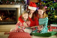Young mother and her little daughters reading a book by a Christmas tree in cozy living room in winter royalty free stock image