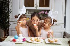 Young mother and her two little daughters with white rabbit`s ears on their heads eat small Easter cakes in the cozy stock images