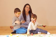Young mother and her two little sons with the paints on their faces dressed in home clothes are sitting on the wooden stock image