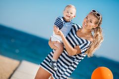 Young mother and her young son on the beach. Royalty Free Stock Image