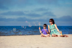 Young mother with his child making soap bubbles Royalty Free Stock Photography