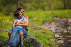 Young mother with his son sit on stone near a stream in a forest Royalty Free Stock Photography