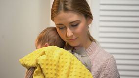 Young mother holding adorable baby in arms, artificial feeding, newborn care. Stock footage stock video footage