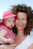 Young mother holding baby daughter. Young smiling mother with curly hair holding her tiny baby daughter, dressed in a red and white check dress and matching hat Stock Image