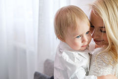 Young mother holding a baby daughter in her arms and kisses her in the nursery Royalty Free Stock Photos