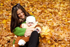 Young mother holding baby in park Royalty Free Stock Photos