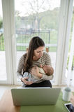 Young mother holding baby son, notebook on table Royalty Free Stock Image