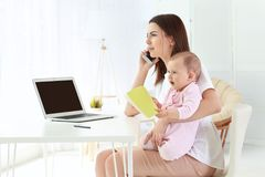 Young mother holding baby while talking on phone in home Royalty Free Stock Photography