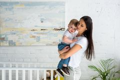 Young mother holding cute baby boy. In hands at home stock image