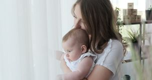 Woman holding baby daughter and looking out through window stock video footage