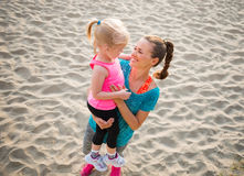 Young mother holding daughter in arms and smiling on the beach Stock Image