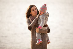 Young mother holding daughter on hands at beach Royalty Free Stock Photography