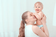Young mother holding her baby. Cute family. Young smiling mother holding her baby above while the child smiles happily and touching the face of the mother Stock Image