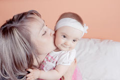 A young mother holding her baby kisses him. Royalty Free Stock Image