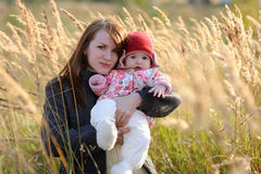 Young mother holding her baby in a meadow. Young mother holding her little baby in a meadow Royalty Free Stock Photography