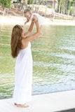 Young mother holding her child in the air. A young mom plays with her daughter by holding her in the air by the lake royalty free stock image