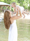 Young mother holding her child in the air. A young mom plays with her daughter by holding her in the air by the lake royalty free stock photo