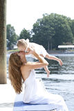 Young mother holding her child in the air. A young mom plays with her daughter by holding her in the air by the lake stock photo
