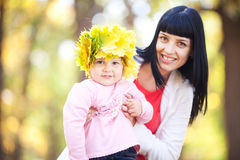 Young mother holding her daughter in a wreath of maple Stock Photos