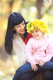 Young mother holding her daughter in a wreath of maple Stock Images