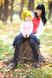 Young mother holding her daughter in a wreath of maple Stock Image