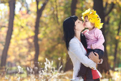 Young mother holding her daughter in a wreath of maple Royalty Free Stock Photography