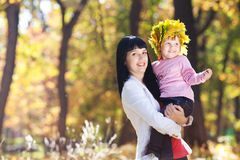 Young mother holding her daughter in a wreath of maple Royalty Free Stock Photo