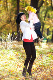 Young mother holding her daughter in a wreath of maple Royalty Free Stock Image