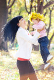 Young mother holding her daughter in a wreath of maple Stock Photo